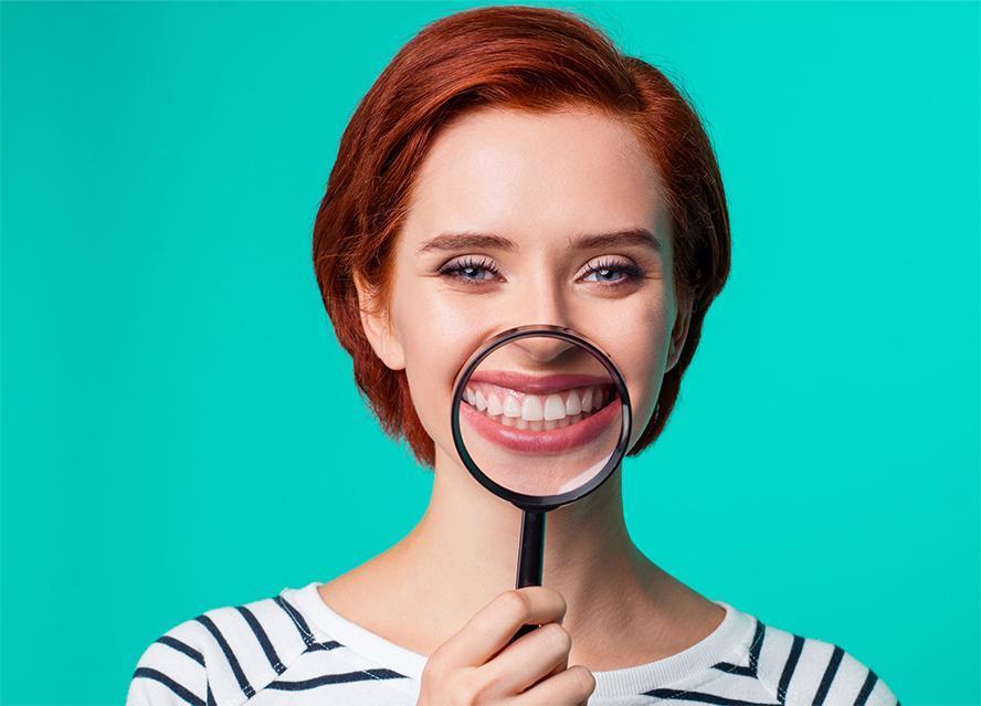 Uśmiechnięta kobieta przykłada lupę dozębów